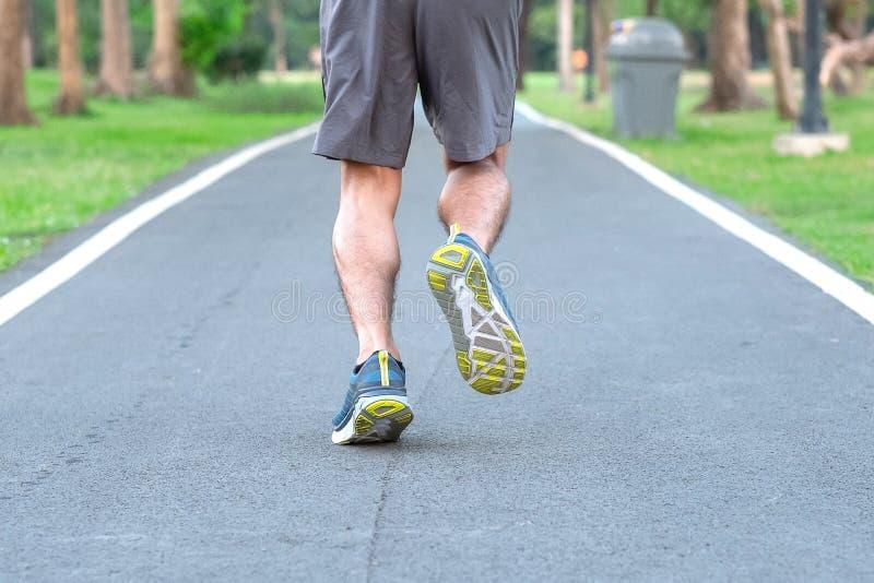 Hombre joven del atleta con las zapatillas deportivas en el parque al aire libre, el corredor masculino que activa en el camino a imagen de archivo libre de regalías