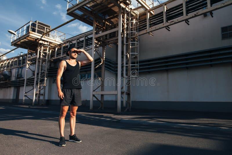 Hombre joven del atleta prepararse para correr y mirar lejos imágenes de archivo libres de regalías