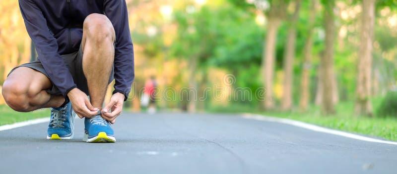 Hombre joven del atleta que ata las zapatillas deportivas en el parque al aire libre, corredor masculino listo para activar en el fotos de archivo libres de regalías