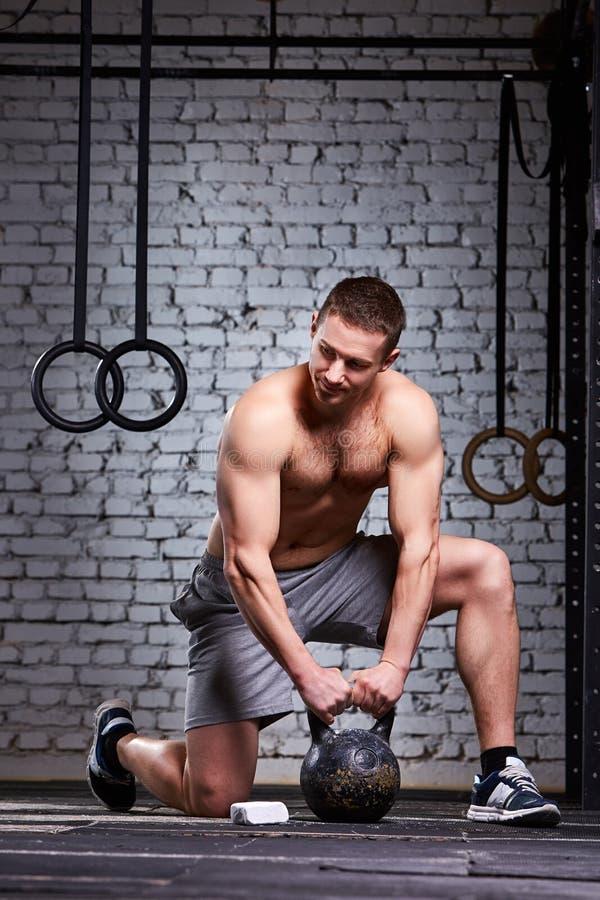 Hombre joven del atleta que lleva a cabo el kettlebell en el piso del gimnasio contra la pared de ladrillo fotografía de archivo libre de regalías