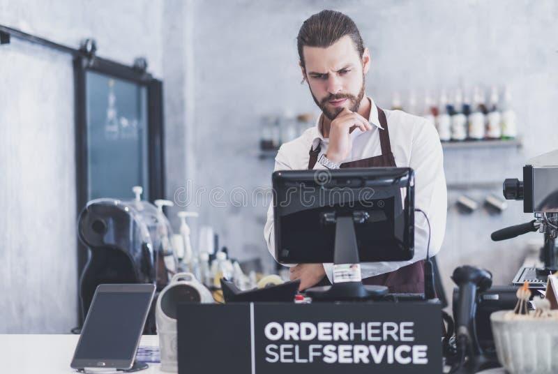 Hombre joven del barista joven confiado que busca un Digital Equipment para pagar el negocio La máquina tiene un problema, ningun fotografía de archivo libre de regalías