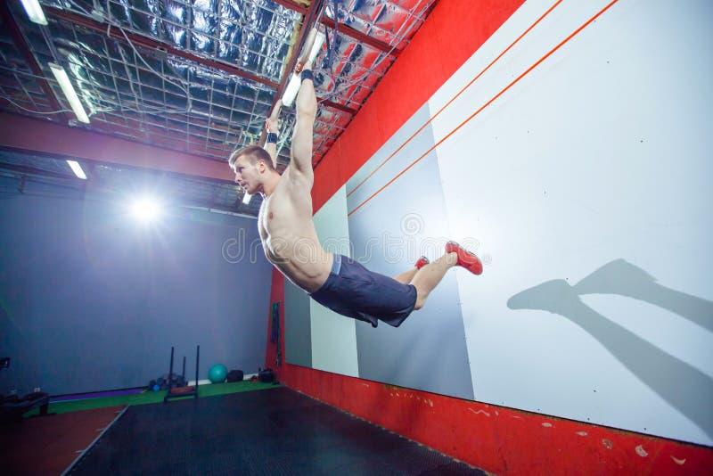 Hombre joven del ejercicio del músculo-para arriba que hace entrenamiento apto de la cruz intensa en el gimnasio en los anillos g fotografía de archivo