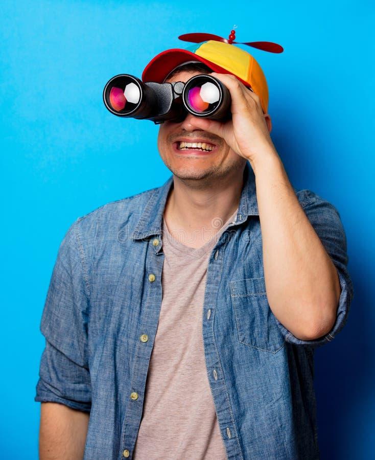 Hombre joven del empollón con el sombrero del noob usando prismáticos foto de archivo libre de regalías