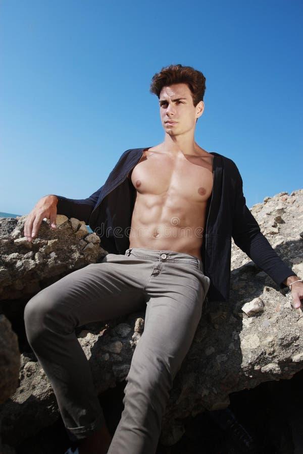 Hombre joven del equipo Abra la camisa y el cuerpo muscular En la roca imagen de archivo