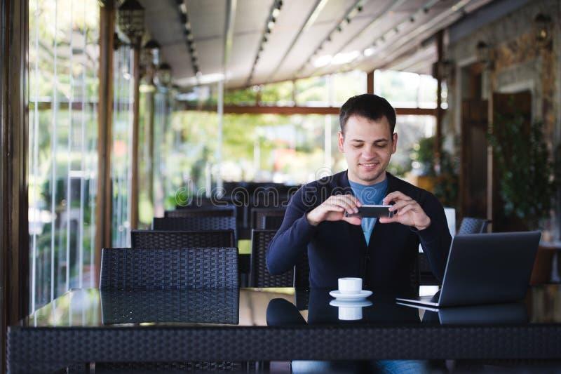 Hombre joven del estudiante que toma la foto de una taza de café y que usa el ordenador portátil en cantina en el café de la univ foto de archivo libre de regalías