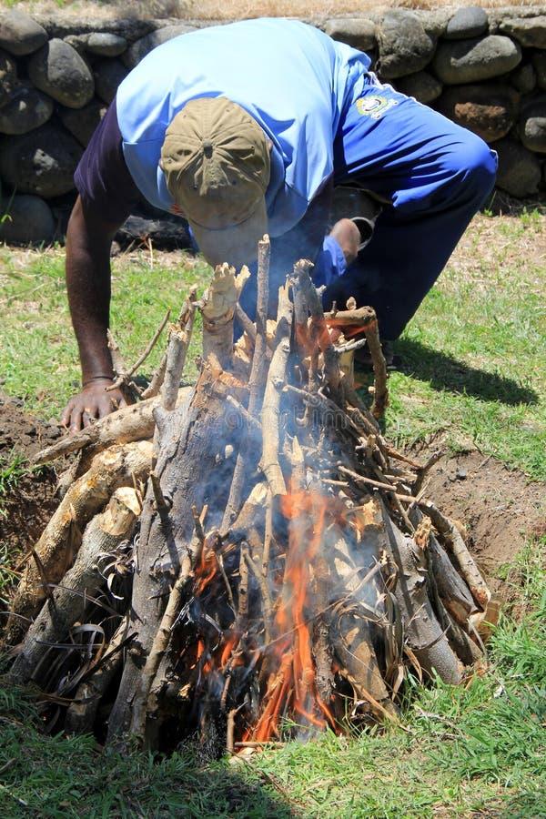 Hombre joven del Fijian que hace el fuego caliente para la celebración tradicional de Lovo, Fiji, 2015 fotografía de archivo libre de regalías
