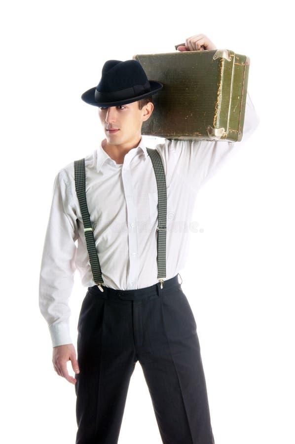 Hombre joven del gángster que sostiene una maleta vieja fotografía de archivo libre de regalías