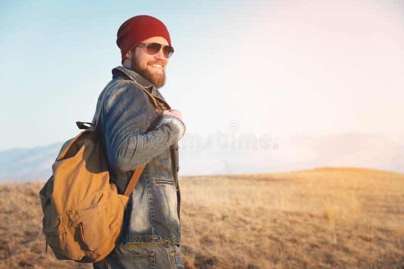 Hombre joven del inconformista con las gafas de sol que llevan de la barba y del bigote que presentan contra la perspectiva de la imagen de archivo