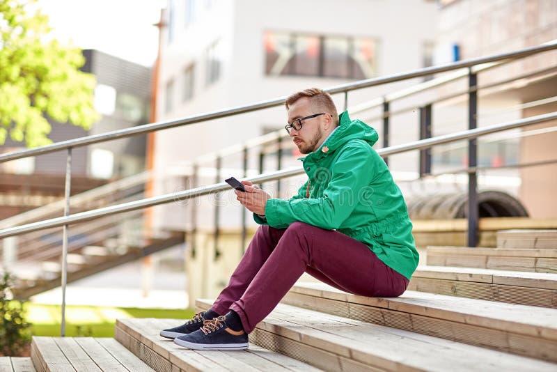 Hombre joven del inconformista con smartphone en ciudad fotos de archivo libres de regalías