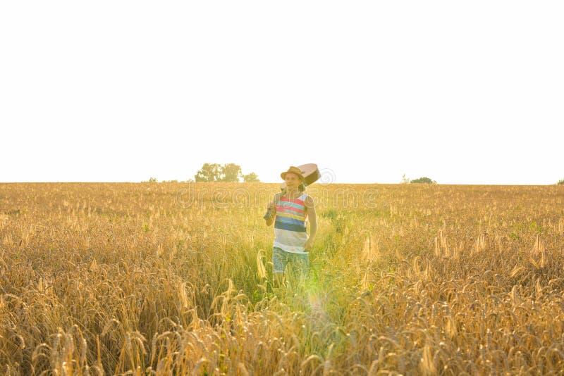 Hombre joven del inconformista que sostiene una guitarra con caminar en la naturaleza, relajándose en el campo en un día soleado fotografía de archivo libre de regalías