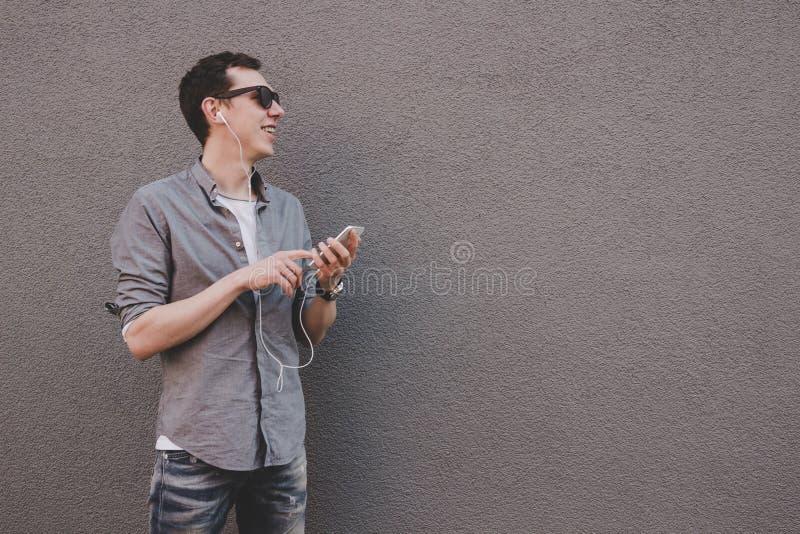Hombre joven del inconformista que usa su smartphone, música que escucha Fondo gris imagen de archivo