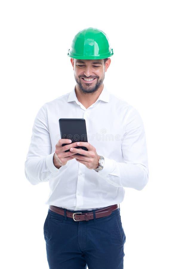 Hombre joven del ingeniero en casco verde usando la tableta aislada foto de archivo libre de regalías