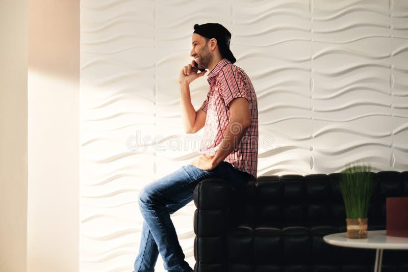 Hombre joven del Latino que habla en el teléfono celular en casa imagenes de archivo