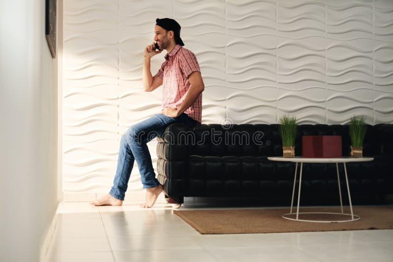 Hombre joven del Latino que habla en el teléfono celular en casa foto de archivo