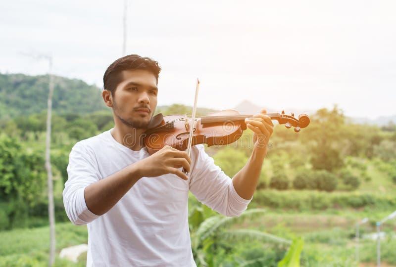 Hombre joven del músico del inconformista que toca el violín en la forma de vida al aire libre de la naturaleza detrás de la mont foto de archivo libre de regalías