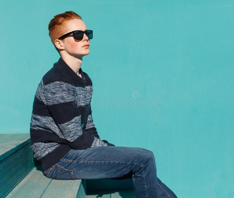 Hombre joven del pelirrojo que se sienta en las escaleras de madera cerca del día soleado caliente del verano de la pared de la t imagenes de archivo