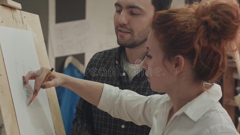 Hombre joven del pintor de la mujer enseñando a cómo dibujar la cara fotos de archivo libres de regalías