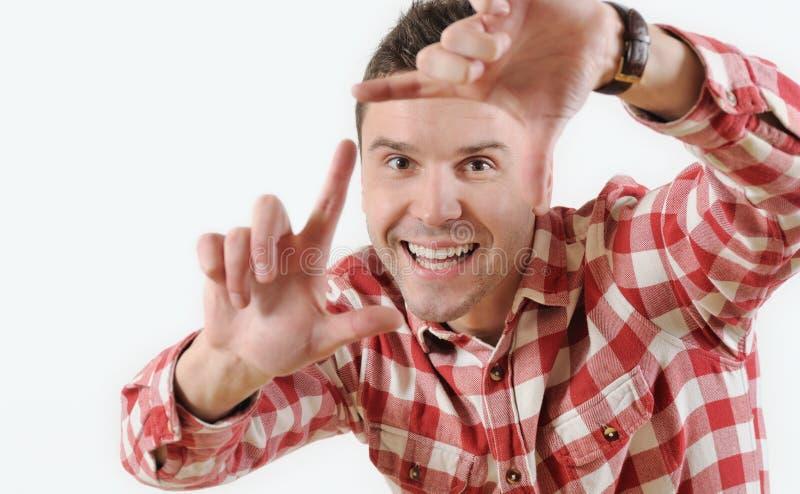 Hombre joven del retrato que muestra el marco del finger que mira la cámara en el fondo blanco imagenes de archivo