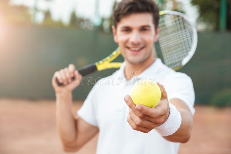 Hombre joven del tenis que da la bola imagenes de archivo