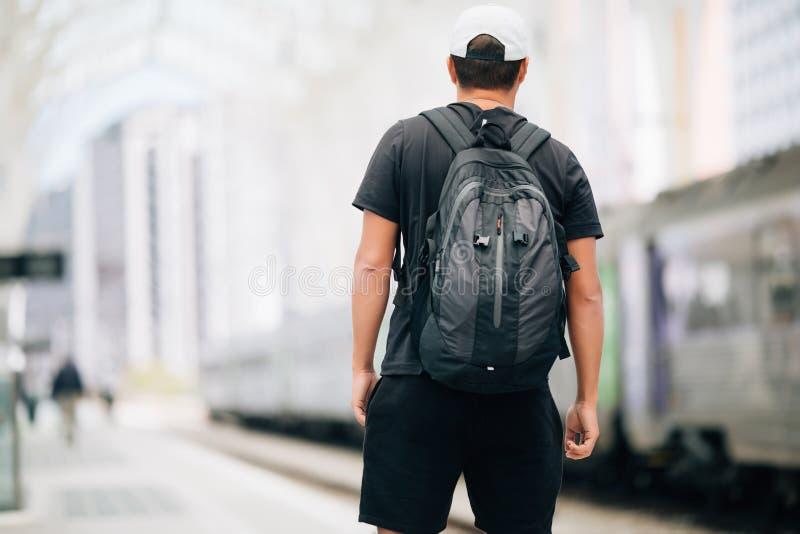 Hombre joven del viajero con la mochila en el ferrocarril en la estación de tren concepto del recorrido imagenes de archivo
