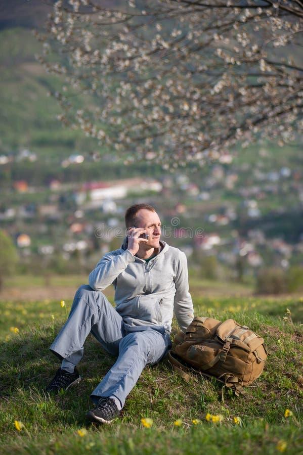 Hombre joven del viajero con la mochila en la colina fotos de archivo libres de regalías