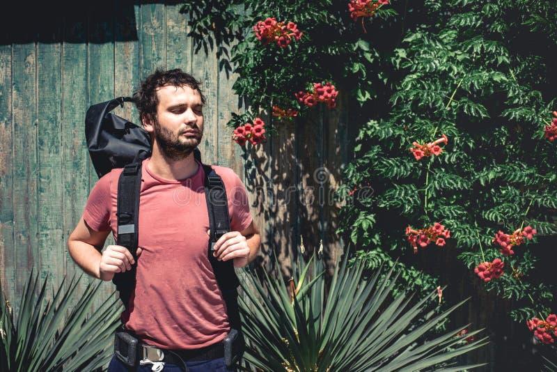 Hombre joven del viajero con la mochila que se coloca cerca de la pared de madera vieja con las plantas imagen de archivo libre de regalías