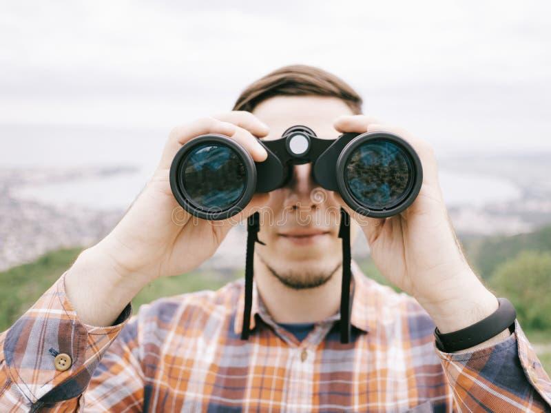 Hombre joven del viajero que mira a través de los prismáticos al aire libre imagen de archivo libre de regalías