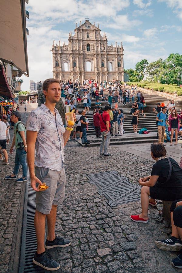 Hombre joven delante de la iglesia del ` s de San Pablo en Macao foto de archivo libre de regalías