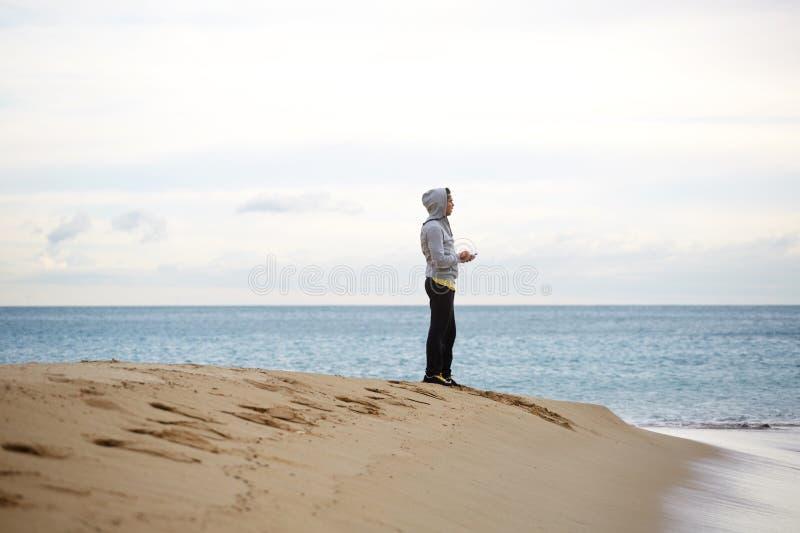 Hombre joven deportivo que se coloca en la playa mientras que toma la rotura durante entrenamiento foto de archivo libre de regalías