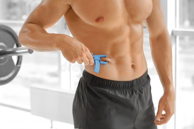 Hombre joven deportivo que usa el calibrador de las grasas de cuerpo imagen de archivo