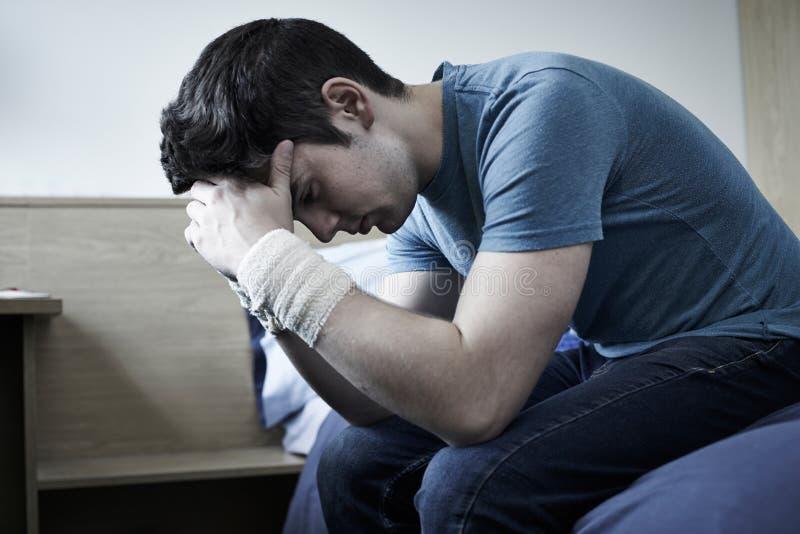 Hombre joven deprimido con las muñecas vendadas después de la tentativa del suicidio imagen de archivo