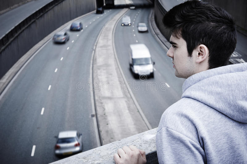 Hombre joven deprimido que comtempla suicidio en el puente del camino foto de archivo