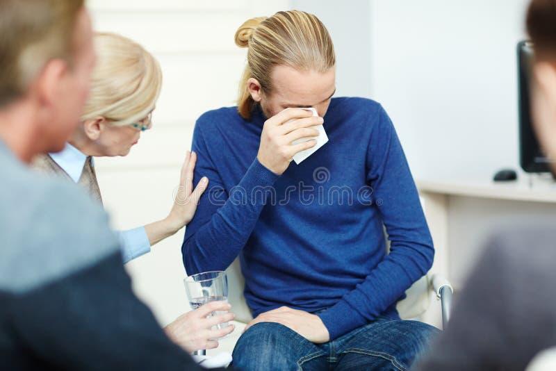 Hombre joven deprimido que llora en terapia del grupo foto de archivo