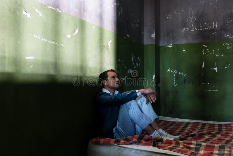Hombre joven deprimido que se sienta en un colchón en una celda de prisión oscura durante custodia fotografía de archivo