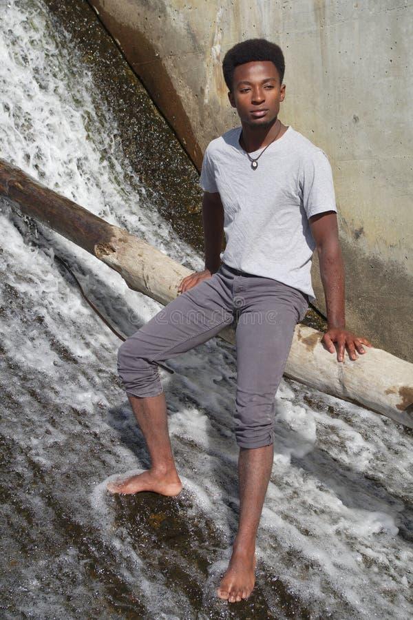 Hombre joven descalzo en el río que se sienta en las cascadas del tronco de árbol fotos de archivo
