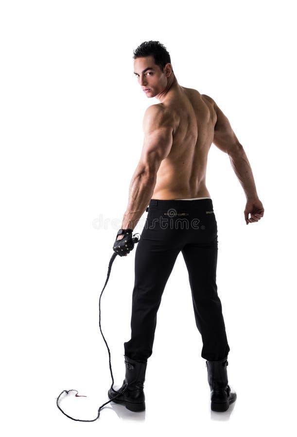 Hombre joven descamisado muscular con el azote y el guante tachonado imagenes de archivo