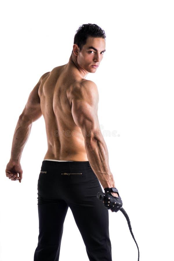 Hombre joven descamisado muscular con el azote y el guante tachonado fotografía de archivo