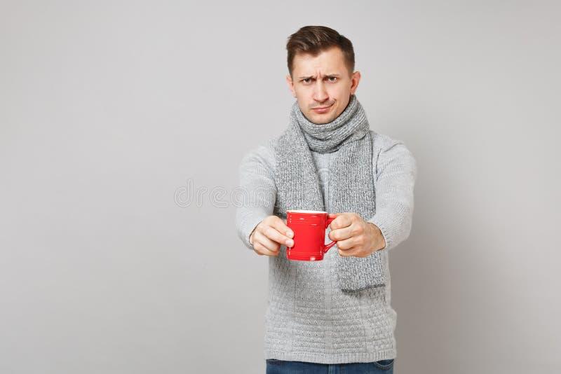 Hombre joven desconcertado en el suéter gris, bufanda que sostiene la taza roja de café o de té aislado en fondo gris en estudio  foto de archivo