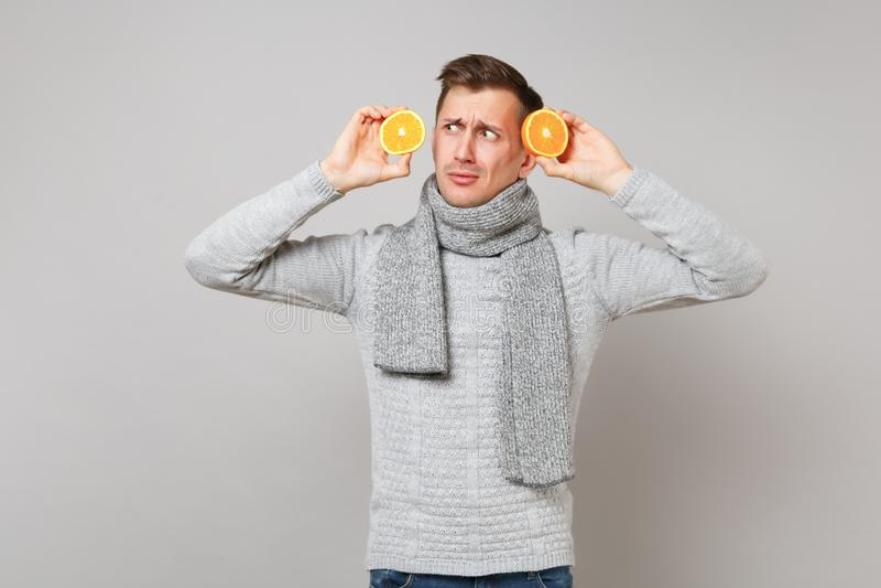 Hombre joven desconcertado en la bufanda gris del suéter que sostiene naranjas cerca de la cara aislada en fondo gris de la pared fotos de archivo libres de regalías