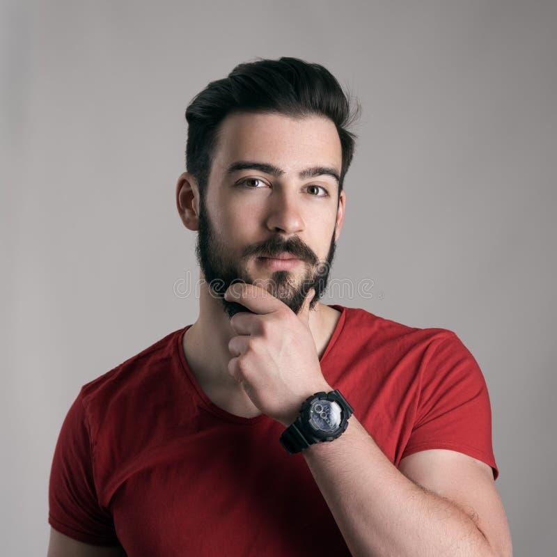 Hombre joven desconcertado que frota ligeramente la barba conmovedora que mira la cámara fotos de archivo libres de regalías