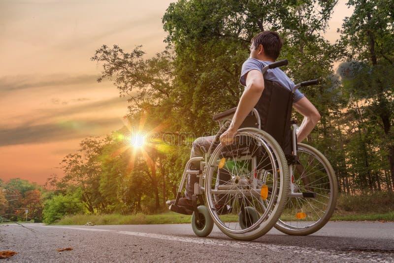 Hombre joven discapacitado o perjudicado en la silla de ruedas en naturaleza en la puesta del sol fotos de archivo libres de regalías