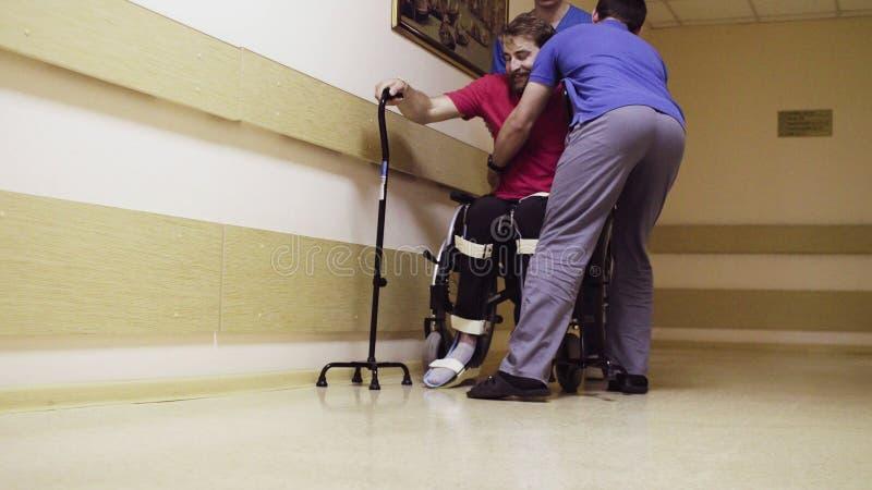 Hombre joven discapacitado que se sienta en una silla de ruedas imagen de archivo