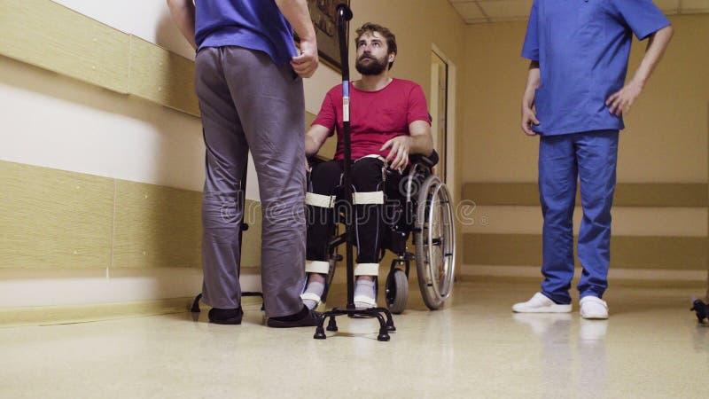 Hombre joven discapacitado que se sienta en una silla de ruedas fotografía de archivo