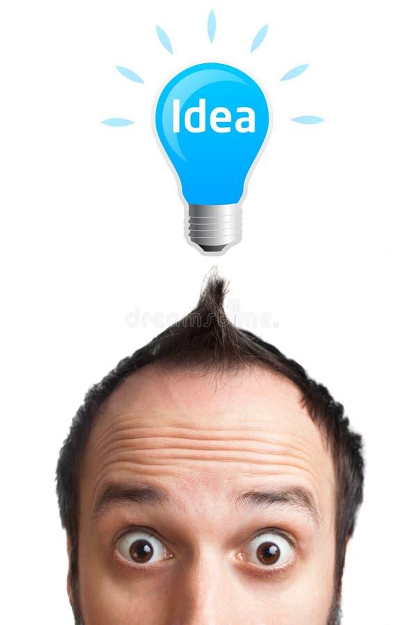 Hombre joven divertido con la bombilla sobre su cabeza foto de archivo libre de regalías