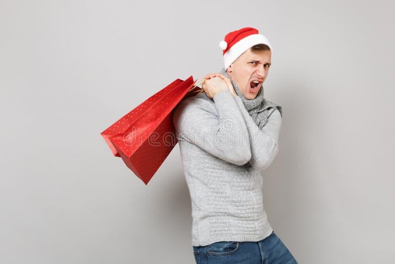 Hombre joven divertido de Papá Noel en bolso rojo del paquete del control del sombrero de la Navidad con los regalos, compras des imágenes de archivo libres de regalías