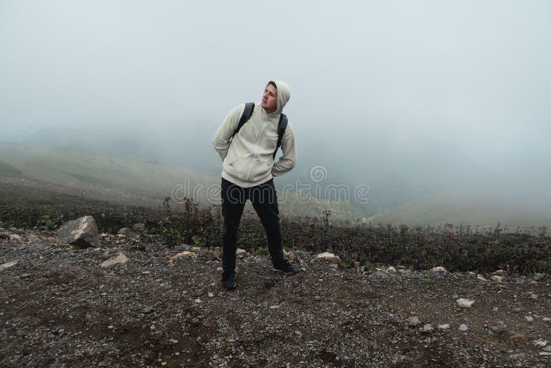 Hombre joven divertido en las monta?as que enga?an alrededor, haciendo caras divertidas y actitudes fotos de archivo libres de regalías