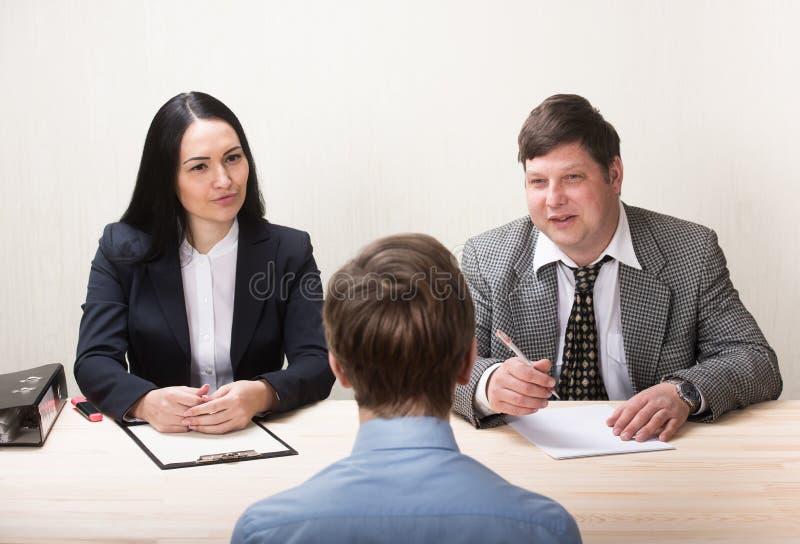 Hombre joven durante entrevista de trabajo y miembros de managemen foto de archivo