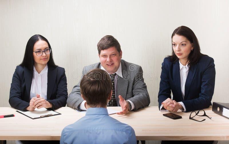 Hombre joven durante entrevista de trabajo y miembros de managemen fotografía de archivo