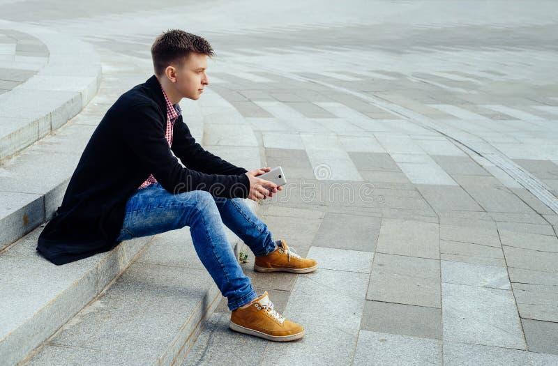 Hombre joven elegante en camisa de tela escocesa y vaqueros que se sientan en las escaleras foto de archivo libre de regalías
