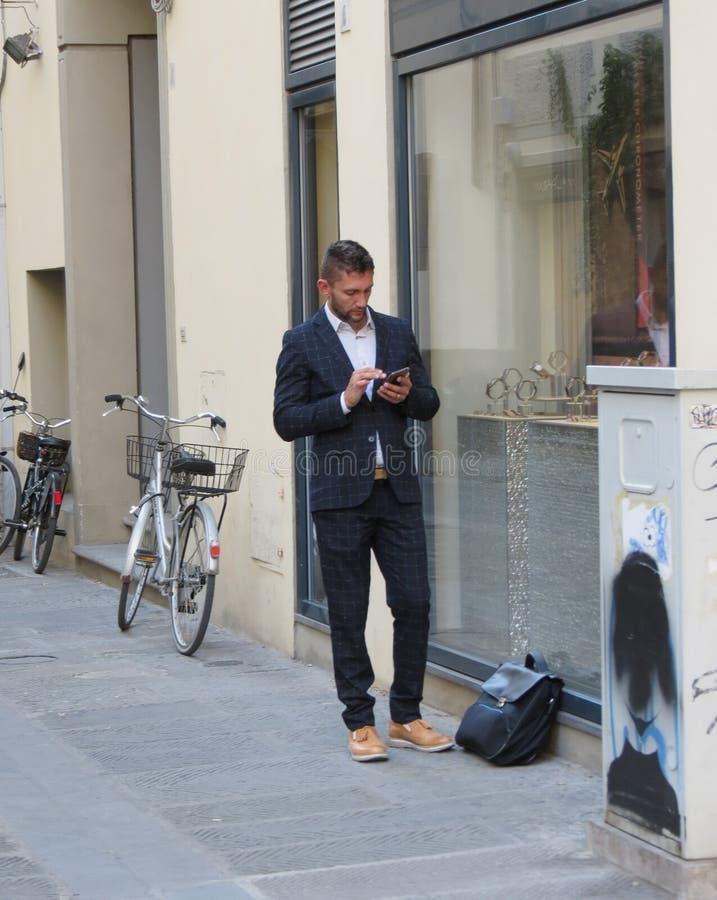 Hombre joven elegante en traje de negocios que invita al móvil foto de archivo